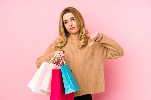 Молодая белокурая женщина, держащая изолированные хозяйственные сумки, показывает жест неприязни, большие пальцы руки вниз.