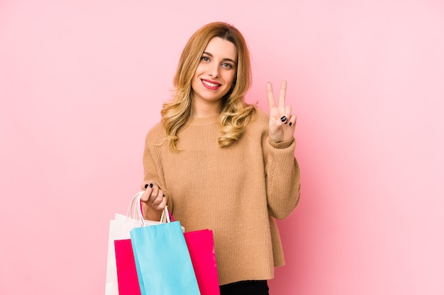 Молодая белокурая женщина, держащая изолированные хозяйственные сумки, показывает номер два пальцами.