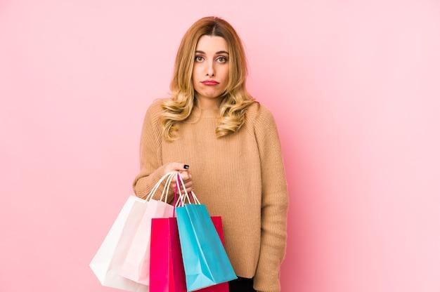 Молодая белокурая женщина, держащая изолированные хозяйственные сумки, пожимает плечами плечами и смущает открытые глаза.