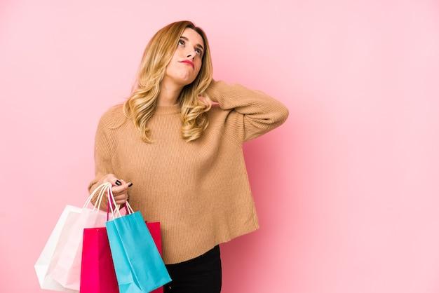 Молодая блондинка женщина, держащая сумки для покупок, изолированные касаясь затылка, думая и делая выбор.