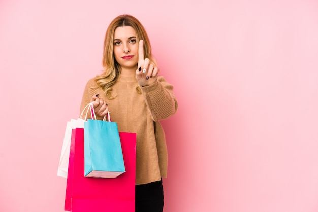 손가락으로 번호 하나를 보여주는 쇼핑 가방을 들고 젊은 금발의 여자.