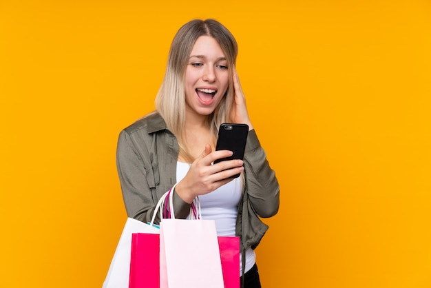 Young blonde woman holding shopping bags and writing a message with her cell phone to a friend