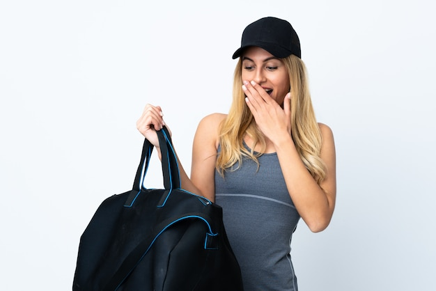 Young blonde woman holding a sport bag on isolated white with surprise and shocked facial expression