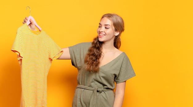 ハンガーにtシャツを保持している若いブロンドの女性