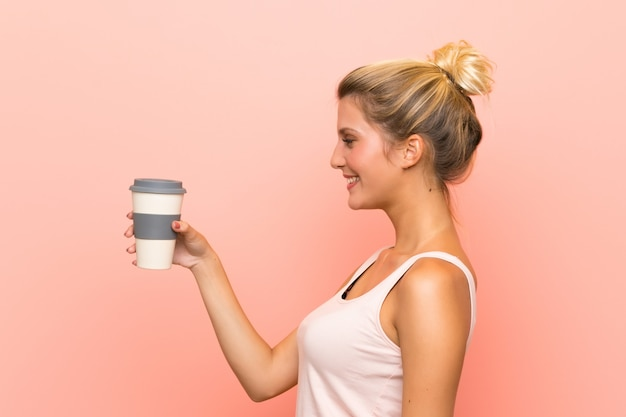 Young blonde woman holding a take away coffee with happy expression
