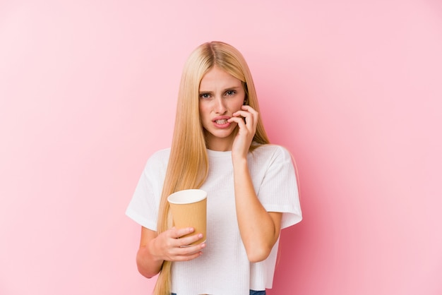 Young blonde woman holding a takeaway coffee biting fingernails, nervous and very anxious
