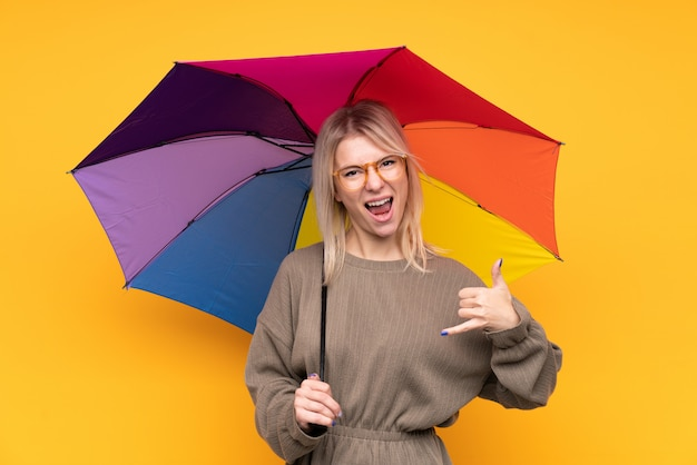 Young blonde woman holding an umbrella over isolated yellow wall making phone gesture