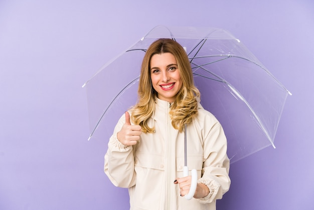Young blonde woman holding an umbrella isolated young blonde woman holding an umbrella isolated smiling and raising thumb up