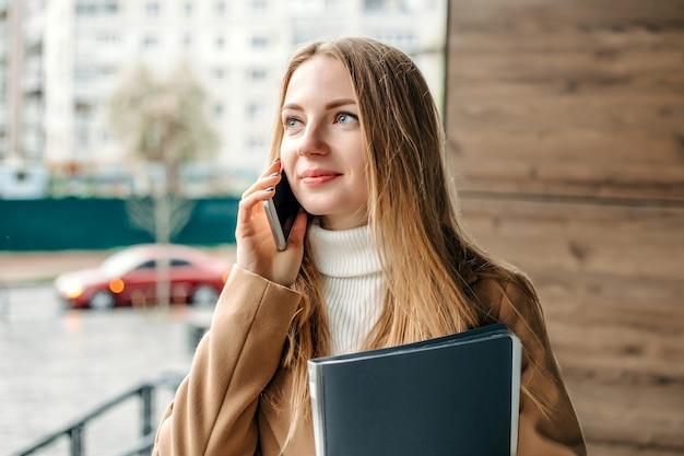 Молодая блондинка женщина в бежевом пальто разговаривает по мобильному телефону, улыбается, держит папку и смотрит в сторону на фоне офисного здания. корпоративный сотрудник. компьютерщик