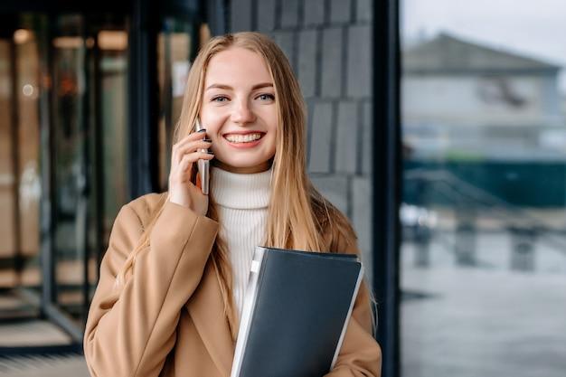 Молодая блондинка женщина в бежевом пальто разговаривает по мобильному телефону, улыбается, держит папку и смотрит в камеру на фоне офисного здания. корпоративный сотрудник. компьютерщик