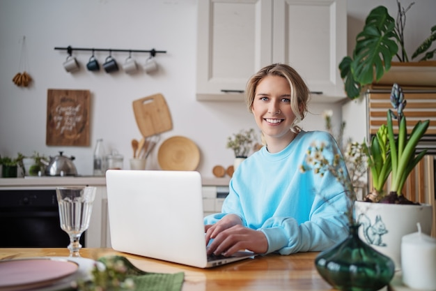파란색 까마귀에 젊은 금발의 여자는 노트북 앞의 부엌에 앉아있다.