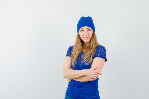 青いtシャツと帽子の若いブロンドの女性