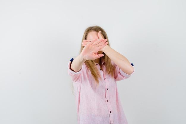 Молодая блондинка в повседневной розовой рубашке закрыла лицо