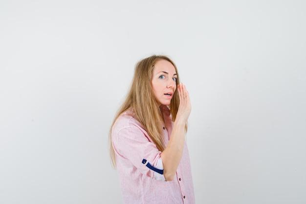 Молодая блондинка в повседневной розовой рубашке шепчет