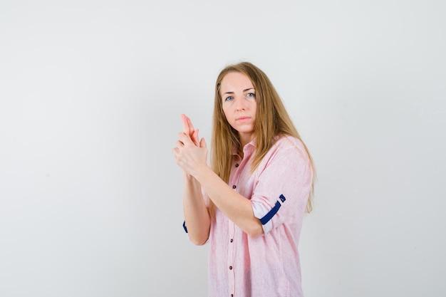 カジュアルなピンクのシャツを着た若いブロンドの女性