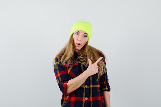 市松模様のシャツと帽子の若いブロンドの女性