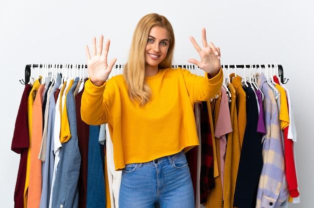 指で8を数える衣料品店の若いブロンドの女性