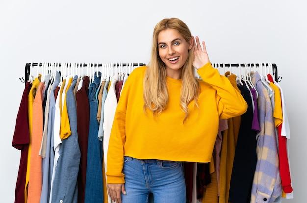 Молодая блондинка в магазине одежды слушает что-то, положив руку на ухо