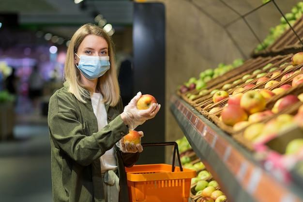 Молодая блондинка женщина в защитной медицинской маске выбирает яблоки, фрукты, овощи на прилавке в супермаркете. женщина, делающая покупки на рынке, стоя возле универмага с корзиной в руках