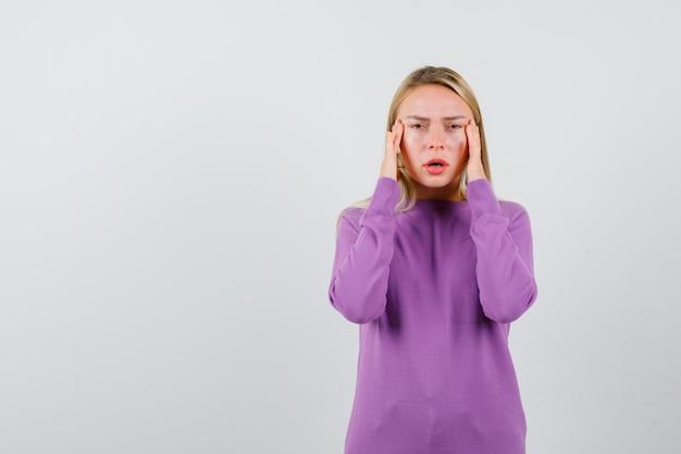 보라색 스웨터에 젊은 금발의 여자