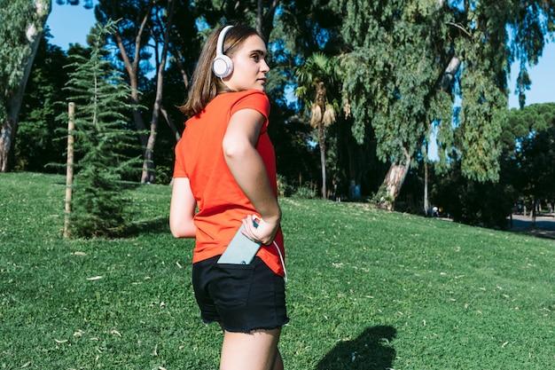 Молодая блондинка в красной рубашке держит мобильный телефон в заднем кармане брюк в парке