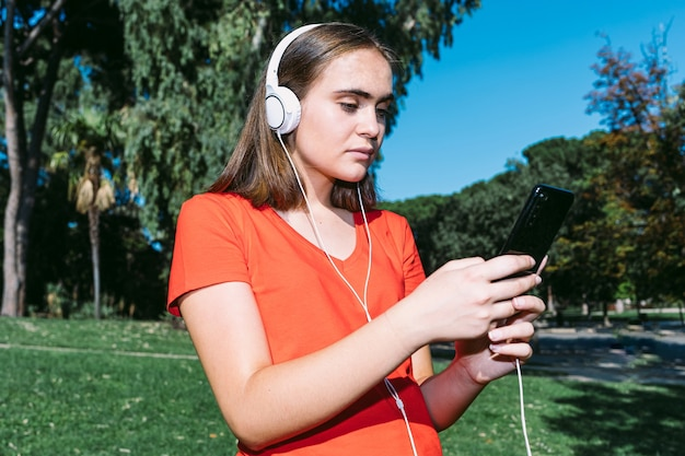 Молодая блондинка в красной рубашке смотрит на мобильный и слушает музыку в наушниках в парке