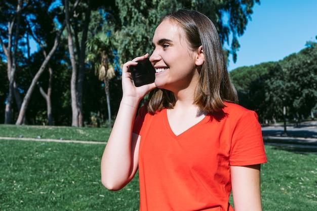 Молодая блондинка в красной рубашке разговаривает по мобильному телефону в парке