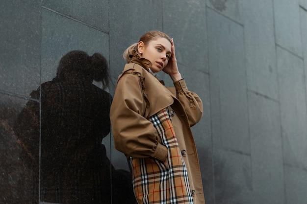 黒のモダンな建物の近くでポーズをとるセーターとベージュのトレンチコートの若いブロンドの女性