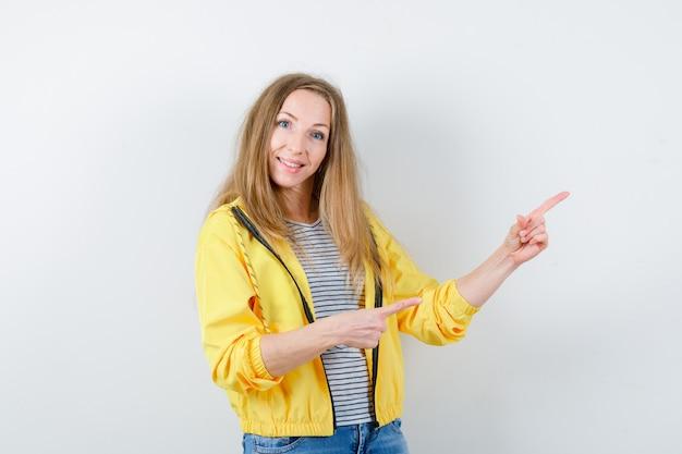 노란색 재킷과 청바지에 젊은 금발의 여자