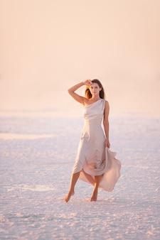 夕方の風通しの良いパステルピンクの粉っぽいドレスを着た若いブロンドの女性は、白い結晶化した塩の上に裸足で立っています。日没時に水の上を歩く岩塩鉱山旅行