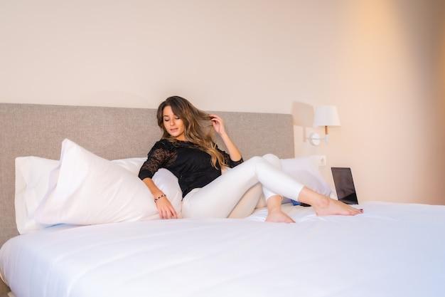 스트리밍 시리즈 채널을 보고 쉬고 있는 노트북으로 집에서 침대에 누워 있는 젊은 금발 여성