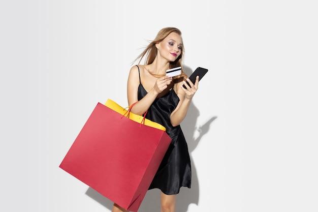 Молодая блондинка в черном платье, делая покупки на белой стене