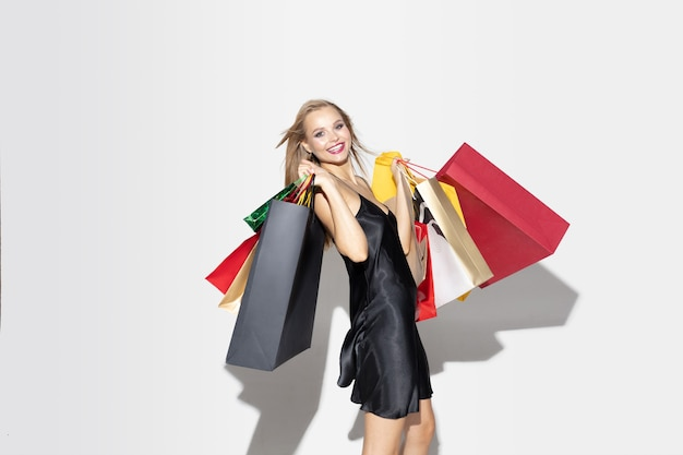 흰 벽에 쇼핑하는 검은 드레스에 젊은 금발 여자.