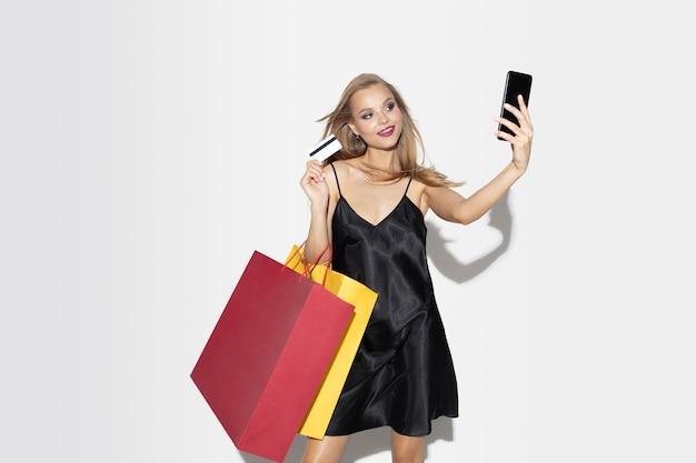 화이트에 검은 드레스 쇼핑에 젊은 금발 여자