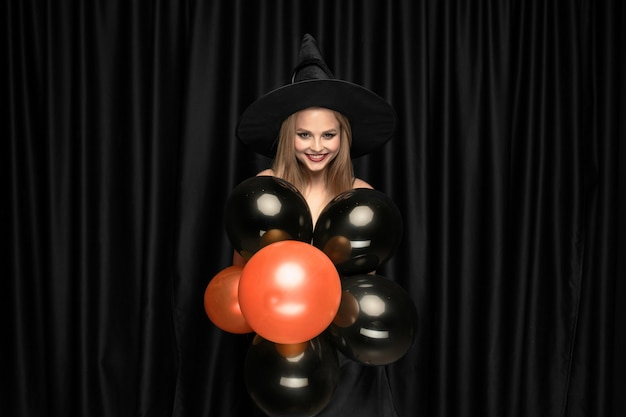 검은 모자와 검은 배경에 의상 젊은 금발의 여자. 매력적이고 관능적 인 여성 모델. 할로윈, 검은 금요일, 사이버 월요일, 판매, 가을