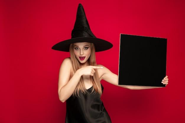 黒の帽子と赤い背景の衣装で若いブロンドの女性。魅力的な白人女性モデルのポーズ。ハロウィーン、ブラックフライデー、サイバーマンデー、販売、秋のコンセプト。コピースペース。黒いプレートを保持します。