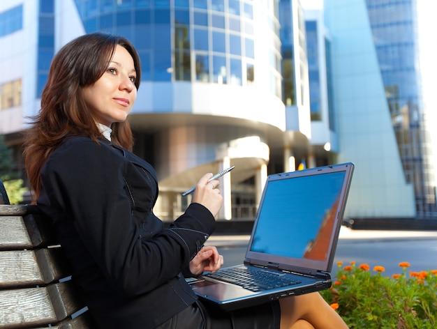 Молодая блондинка в деловой одежде сидит на скамейке с ноутбуком в ясный летний день