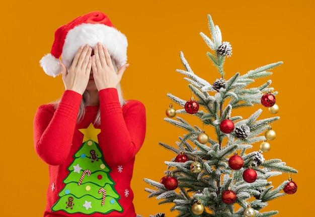 Молодая блондинка в рождественском свитере и шляпе санта-клауса c