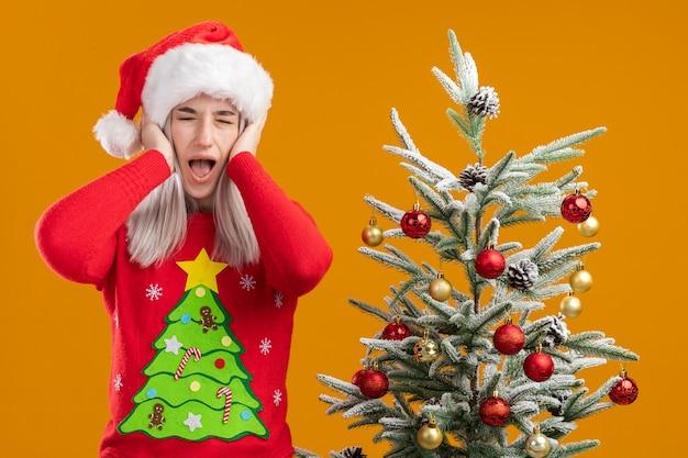 オレンジ色の背景の上のクリスマスツリーの横に立っているイライラした表情で手で耳を覆うクリスマスセーターとサンタ帽子の若いブロンドの女性