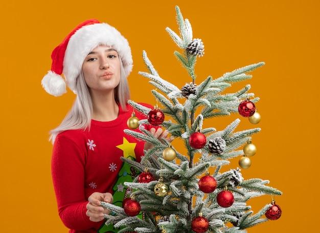 Молодая блондинка в рождественском свитере и шляпе санта-клауса, украшающая елку, счастливая и позитивная, дует воздушный поцелуй, стоя на оранжевом фоне