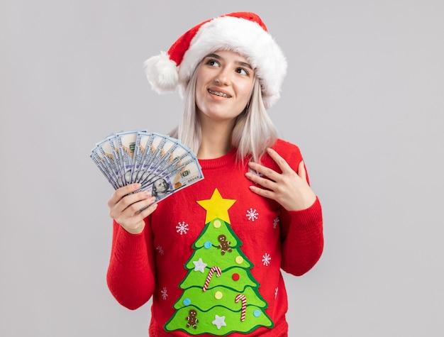 クリスマスセーターとサンタ帽子の若いブロンドの女性は、感謝の気持ちで幸せそうな顔で見上げる現金を保持しています