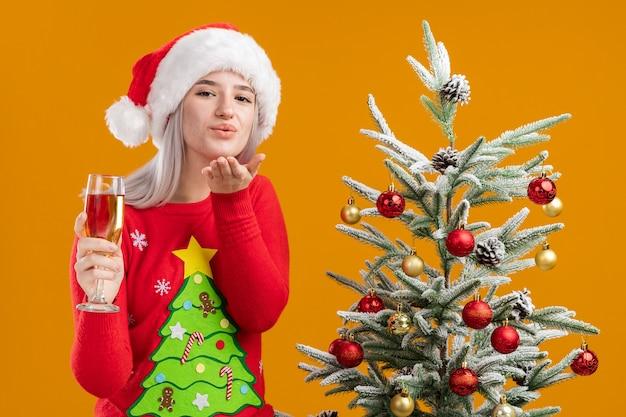 Молодая блондинка в рождественском свитере и шляпе санта-клауса с бокалом шампанского счастлива и позитивно дует воздушный поцелуй, стоя рядом с елкой на оранжевом фоне