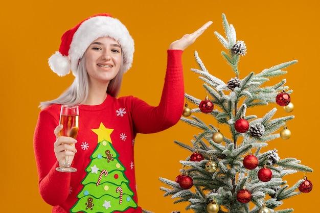 オレンジ色の壁の上のクリスマスツリーの横に立って腕を上げて幸せで前向きな笑顔のシャンパンのガラスを保持しているクリスマスセーターとサンタ帽子の若いブロンドの女性