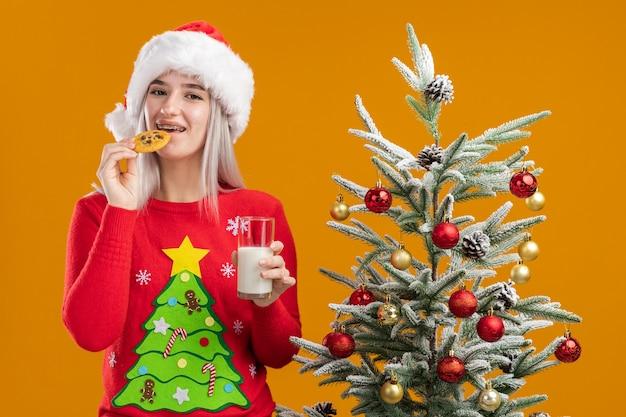 幸せでポジティブなクッキーを食べる牛乳のガラスを保持しているクリスマスセーターとサンタ帽子の若いブロンドの女性