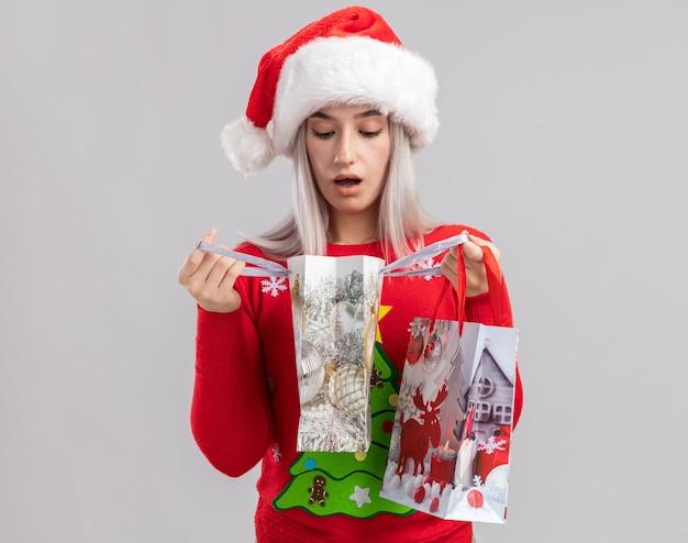 クリスマスのセーターとサンタの帽子をかぶった若いブロンドの女性が興味をそそられるように見えるクリスマスの贈り物を開く紙袋と