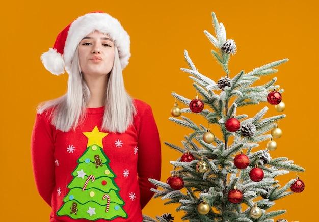 Молодая блондинка в рождественском свитере и шляпе санта-клауса смотрит в камеру, счастливая и позитивная, дует воздушный поцелуй, стоя рядом с елкой на оранжевом фоне