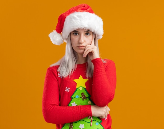 オレンジ色の背景の上に立っている深刻な顔でカメラを見てクリスマスセーターとサンタ帽子の若いブロンドの女性