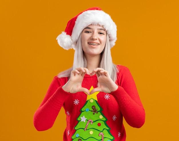 オレンジ色の背景の上に立っている指でハートジェスチャーを作る幸せな顔に笑顔でカメラを見てクリスマスセーターとサンタ帽子の若いブロンドの女性