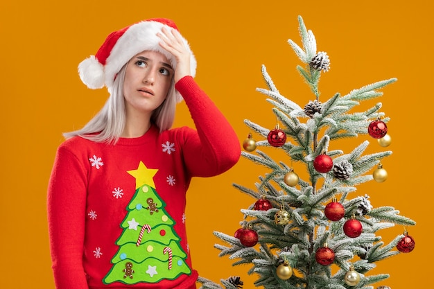 クリスマスセーターとサンタの帽子の若いブロンドの女性は、間違いのために彼女の頭の上の手と混同して見上げる