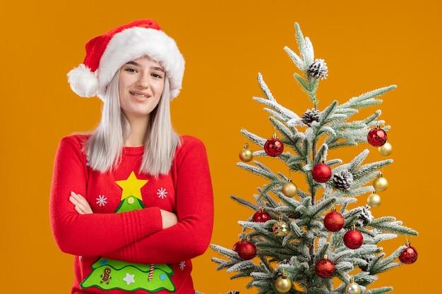 Молодая блондинка в рождественском свитере и шляпе санта-клауса с уверенным выражением лица со скрещенными руками